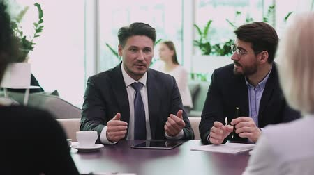 persuasion : Confident businessman ceo coach mentor wear suit negotiating with partners speaking to clients investors at business meeting conference table presenting corporate project teaching staff in office Stock Footage