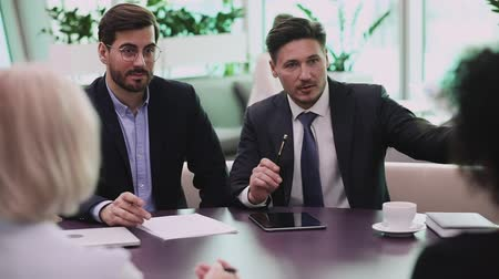 persuasion : Male businessman conference leader ceo wear suit and tie consulting clients negotiate with partners talking to business team explain project plan discuss financial strategy sit at group meeting table Stock Footage