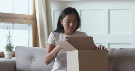 hediyeler : Excited asian female consumer opening parcel cardboard box receiving online shop fragile postal shipment order, happy ethnic girl customer satisfied with good purchase fast courier delivery concept Stok Video