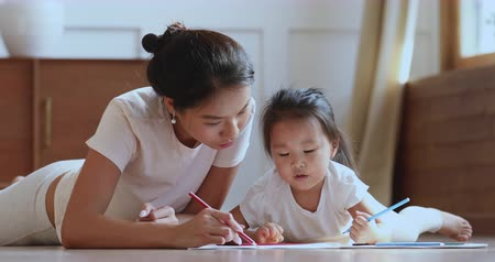 babysitter : Caring young asian ethnic mum or nanny helping cute kid daughter teaching toddler child daughter drawing picture with pencils lying on warm heated floor in bedroom learn creative art activity at home