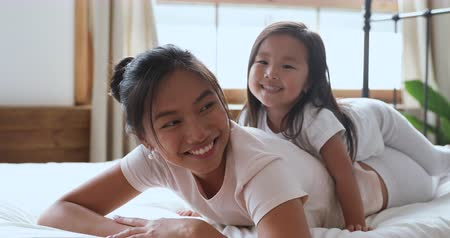 omzunda : Happy affectionate cute asian family young mother and cute little kid daughter laughing bonding in bed, adorable small ethnic child girl lying on moms back having fun cuddling looking at camera
