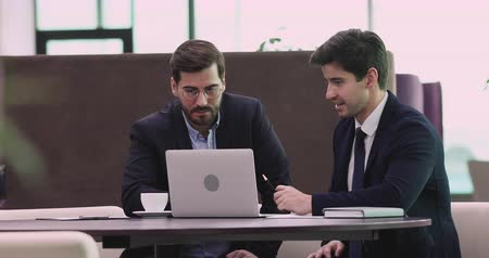 öğretim : Young businessman executive financial investment advisor wear suit showing presentation on laptop consulting business investor client about software trading shares data sit at office table meeting Stok Video