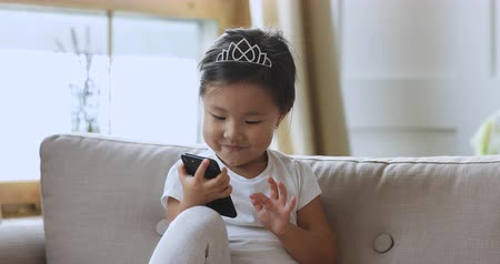 obsession : Curious cute smart small asian child girl sit alone on sofa hold smartphone learning using tech obsessed with gadget concept, little vietnamese kid play mobile game having fun in app internet at home Stock Footage
