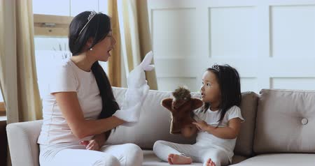 babysitter : Cute little asian child girl wear crown playing puppet theatre holding animals on hands with young adult mother at home, ethnic parent or babysitter and kid daughter telling fairy tale game with toys Stock Footage