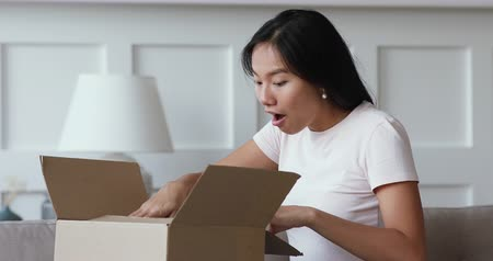 доставлять : Happy amazed young asian girl consumer holding opening cardboard box sit on sofa at home, excited vietnamese woman customer receive unbox good parcel, order postal shipping courier delivery concept