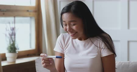 fertilidade : Excited pregnant young asian woman hold look at positive pregnancy test feel great surprise sit on sofa at home, happy vietnamese lady expect baby, fertility pregnancy in vitro fertilization concept Vídeos