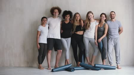 leden : Full length view seven multi-ethnic cheery young friends girls and guys embracing standing leaned on wall waiting for yoga class, finished work out feels happy, on floor lot of mats, wellness concept