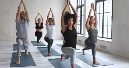 hatha : Diverse sportive people taking part at yoga session led by African coach performing Warrior I pose Virabhadrasana. Beginners practicing training together with instructor raised hands stretching body