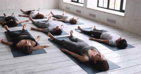 restorative : Multi-ethnic young people wearing gray and black sportswear practising yoga do Corpse Savasana exercise Dead Body pose lying on mat indoors relaxing after workout in sport club. Hobby wellness concept