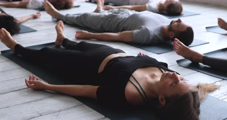 ziel : Close up focus on caucasian woman lying on mat during session with other multi-ethnic people practicing Savasana or Dead Body Corpse Pose, final asana of yoga class deep restoration, wellness concept