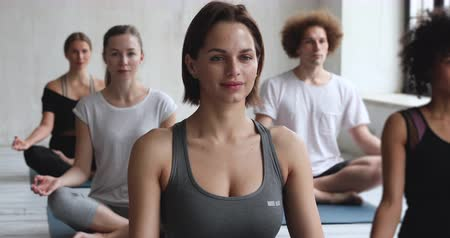 en tête : Caucasian female yoga coach and multiracial people meditating seated in lotus position indoor, do breath technique calming mind and body enjoy relaxation process, lifestyle healthy life habits concept Vidéos Libres De Droits