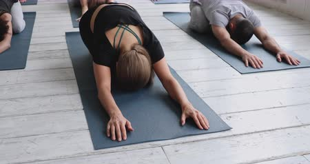 relieve : Group of young multi-ethnic people practicing yoga exercise with caucasian instructor lying on mats performing Balasana or Child pose, working out in sport club. Well-being, wellness lifestyle concept