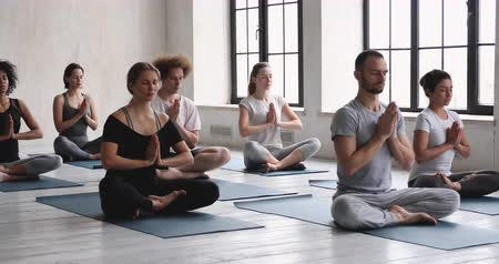 инструктор : Male coach and group of diverse people seated in lotus pose folded hands Namaste symbol practicing yoga meditating during class, prayer position, spiritual practice, lifestyle life philosophy concept