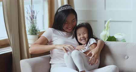 humor : Cheerful loving young asian mom tickling cute small child daughter laughing cuddling sit on sofa, happy vietnamese family mother and kid wear crowns playing funny game together having fun on couch Stock mozgókép