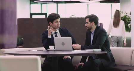 komisyoncu : Two friendly businessmen partners wear suits colleagues team discuss online startup idea working together in teamwork planning collaboration having business conversation sit at table in modern office Stok Video