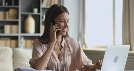 talep : Smiling young business woman professional talking on phone using laptop sit at home office desk, happy female customer make mobile call confirming online website shopping order delivery concept