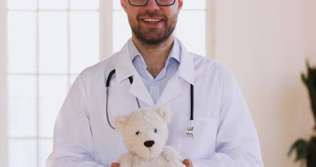 paediatrician : Qualified trusted caring male doctor pediatrician or veterinary hold teddy bear animal toy looking at camera, smiling man professional medic practitioner surgeon wear white uniform posing in hospital