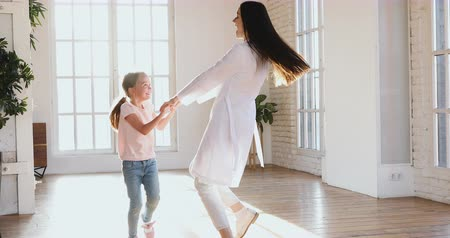 kinderarts : Carefree funny little kid girl patient and female nurse doctor pediatrician babysitter wear white coat holding hands having fun dancing spinning laughing at home hospital room enjoy playing together Stockvideo