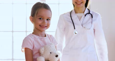 小児科医 : Female professional doctor pediatrician wear white coat come to happy cute little child girl embrace kid patient hold toy look at camera, children healthcare and paediatric medical treatment concept