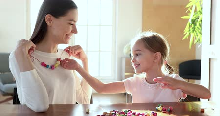 nanny holding : Happy cute small child daughter making necklace of multicolored beards for young adult mom, funny preschool little kid girl learning creative activity with mother babysitter playing together at home