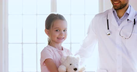 小児科医 : Caring male doctor pediatrician wear white uniform hugging little cute child girl patient hold toy look at camera, children healthcare professional medic treatment and protection concept, portrait