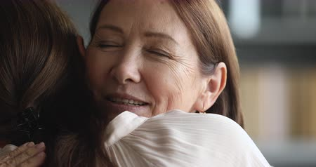 понимание : Caring senior mature beautiful mom hugging adult grown young daughter enjoying cuddling embracing with eyes closed, two generations women family reunion and sweet tender mothers love concept, closeup
