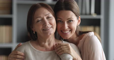 stary : Beautiful caring adult daughter hugging senior mature mum bonding together looking at camera indoors, loving smiling two older and young age generation women embracing at home, close up portrait