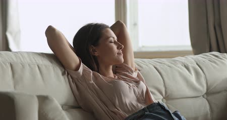 trecho : Calm relaxed healthy young woman resting on sofa holding hands behind head eyes closed take deep breath of fresh air dream lounge on couch at home feel no stress concept enjoy comfort welfare at home