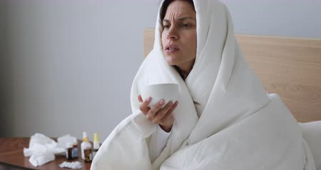 baca : Unhealthy mixed race girl sitting on bed, covered in blanket, holding cup of hot tea. Unhappy ill sick young woman caught cold, freezing under duvet, treating herself with medicine alone at home.