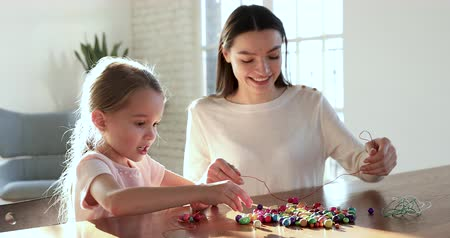 naszyjnik : Cute preschool little daughter learning creative activity holding string making necklace of multicolored beards with young mom babysitter helping teaching small child girl playing together on daycare