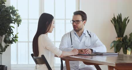 health insurance : Male professional doctor physician wear white uniform talk to young adult woman patient explain diagnosis treatment at medical checkup consultation in clinic office, medicine and health care concept