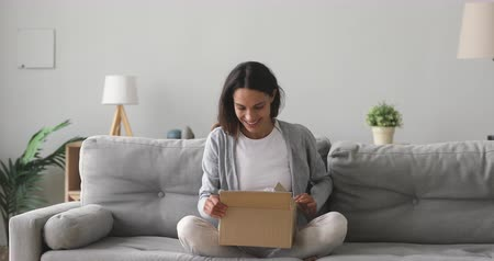 recibidor : Smiling satisfied female client unpacking postal package, sitting on couch at home. Happy young mixed race woman unboxing wished item, purchased goods from popular internet store in living room.
