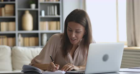 conferencing : Smiling female online tutor counselor english teacher wear wireless earphone speaking teaching web class doing conference video call chat on laptop make notes communicate by webcam at home office