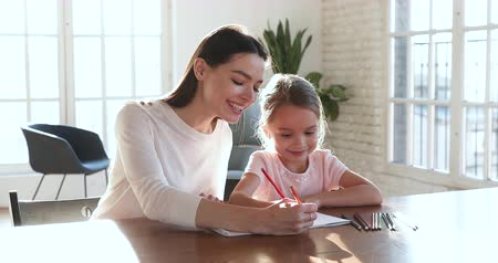 babysitter : Smiling young female babysitter mom teaching happy cute kid daughter drawing color pencils together, happy adult mother teacher help little girl enjoy creative child care activity concept at home Stock Footage