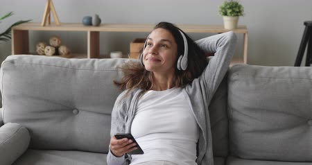 wearing earphones : Happy young mixed race woman wearing wireless headphones, relaxing on cozy sofa, listening to music. Smiling girl choosing favorite tracks in mobile app, relaxing on comfortable couch in living room.