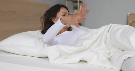 хмурый : Stressed mixed race woman waking up in morning, sitting on bed, rubbing lower back. Unhappy young lady feeling strong ache, suffering from fibromyalgia after sleeping on uncomfortable mattress.