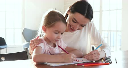nanny : Caring mom babysitter hug help cute preschool little kid daughter drawing coloring picture holding pencils sit at table, happy mother teach child girl learn creative art activity bonding at home