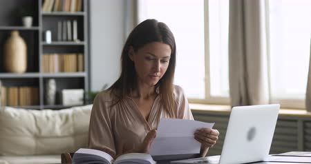 factuur : Excited amazed young lady customer open read paper letter feel overjoyed receive good news got new job opportunity salary payment tax refund concept loan approval message sit at home office desk