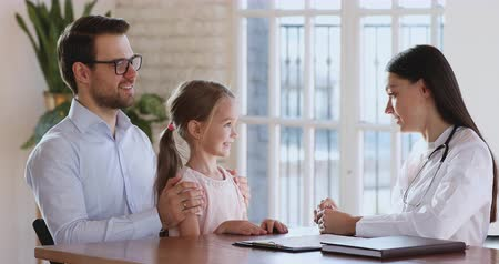 paediatrician : Young woman pediatrician and cute little kid girl patient talk at paediatric checkup, female doctor explaining children healthcare to preschool child with parent visiting medical consultation concept Stock Footage