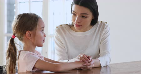 begrijpen : Caring young mother children psychologist hold hand talk comforting sad kid girl child daughter help with problem give psychological support in trust honest conversation at therapy session concept