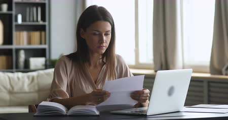 factuur : Frustrated shocked young woman feel upset read bad news in paper letter sit at home office desk, stressed worried lady receive post mail notice about financial problem in bank debt bill tax invoice