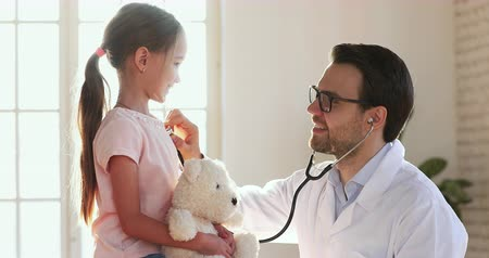 paediatrician : Smiling male medic pediatrician holding using stethoscope examining cute little child girl patient holding toy, happy man doctor listening kid heartbeat do pediatric checkup concept at home hospital Stock Footage