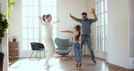 ailelerin : Active carefree young adult parents and small preschooler kid daughter dancing together at home, happy family with little cute child jump to music enjoy leisure lifestyle in modern sunny living room Stok Video