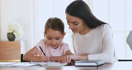 babysitter : Young mom tutor teach help cute school child daughter learn writing doing homework sit at home table, teacher with preschool kid girl study together, parents and children elementary education concept Stock Footage