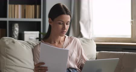 factuur : Young woman holding papers using laptop computer paying bills invoice online at home, focused adult lady customer user doing paperwork making bank loan payment in internet app on website sit on sofa
