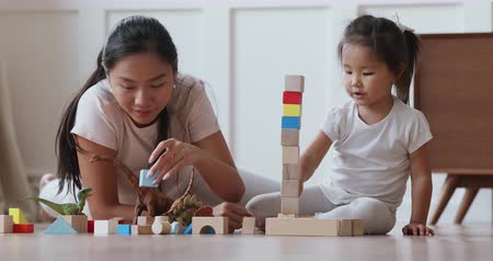 детский сад : Happy vietnamese family asian mum daycare babysitter playing with focused cute small kid daughter help building castle of wooden blocks having fun talking laughing lying on warm floor in living room Стоковые видеозаписи