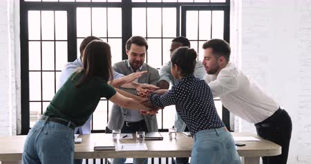 membro : Happy reliable multi ethnic team staff business group stack hands together over meeting table express teamwork concept, strength in professional support, corporate partnership, power of collaboration