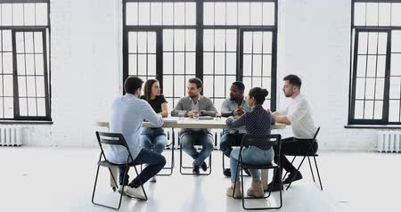 intérieur de bureau : Confident male leader executive ceo manager speak at group meeting in modern conference room sit at office table training multiethnic business team discussing project plan at corporate staff briefing