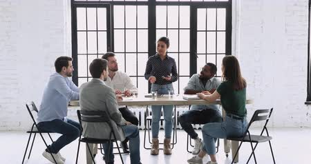 warsztat : Happy indian female startup leader talking to multiracial team people having fun at office meeting, friendly multi ethnic employees group laughing discussing corporate project ideas at briefing table