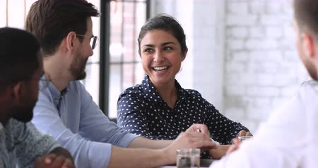trabalho em equipe : Smiling indian businesswoman hr team member executive talking to male job applicant coworker having professional friendly business discussion during employment interview, group meeting or negotiation
